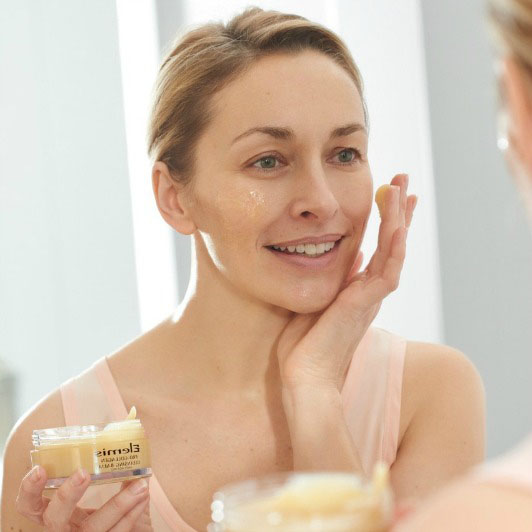 mature woman applying elegies cleansing balm